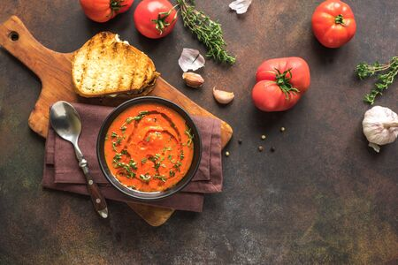 Tomato Soup with grilled cheese sandwich, top view, copy space. Homemade tomato soup with thyme.