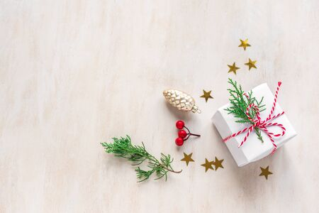 Christmas composition. Christmas gift, fir branches and golden stars on white wooden background. Flat lay, top view, copy space. Imagens
