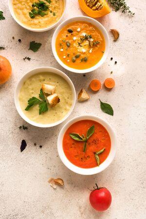 Soup Assortment. Set of various seasonal vegetable soups and organic ingredients, top view, copy space. Homemade colorful vegan vegetarian soups. Imagens