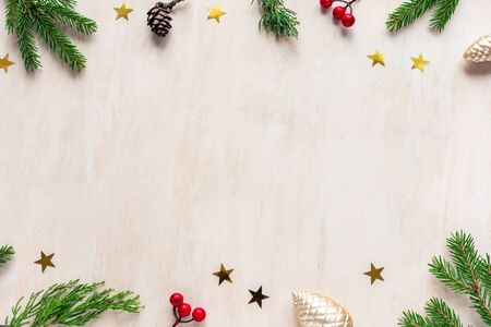 Christmas composition. Christmas  pine cones, fir branches and golden stars on white wooden background. Flat lay, top view, copy space.