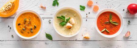 Soup Assortment. Set of various seasonal vegetable soups and organic ingredients, banner, copy space. Homemade colorful vegan vegetarian soups. Imagens