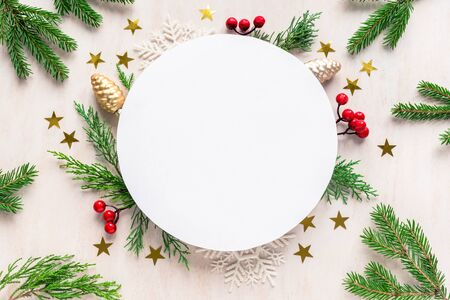 Christmas composition with round copy space. Christmas gift, pine cones, fir branches on white wooden background. Flat lay, top view.