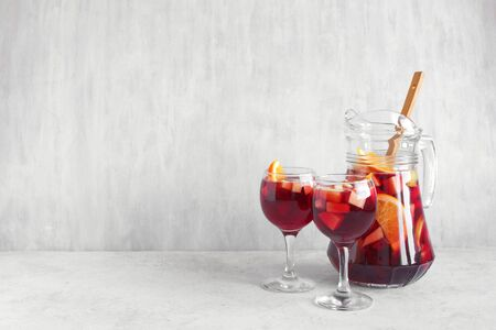 Red wine sangria or punch with fruits and ice in glasses and pitcher. Homemade refreshing fruit sangria on white background, copy space. Stok Fotoğraf