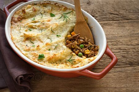 Shepherds Pie with ground beef, potato and cheese on wooden background, top view, copy space. Traditional homemade casserole - Shepherds Pie.