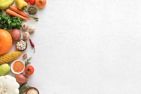 Vegetarische kookachtergrond met seizoensgebonden biologische groenten en granen op wit, bovenaanzicht, banner. Ingrediënten voor vegan vegetarische seizoenssoepen en gerechten.