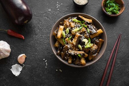 Stir fried aubergine in bowl. Corean, chinese or asian vegan meal - eggplant stir fry with soy sauce sweet glaze, top view, copy space.