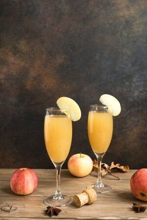 Apple Mimosa Cocktail in tall glasses and organic apples on dark, copy space. Seasonal fall drinks - champagne mimosa cocktail with apples. Archivio Fotografico