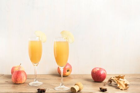 Apple Mimosa Cocktail in tall glasses and organic apples, copy space. Seasonal fall drinks for holidays - champagne mimosa cocktail with apples.