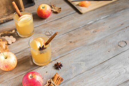 Spicy Apple Cider Drink. Seasonal autumnal homemade apple cider on wooden table, copy space. Stock Photo