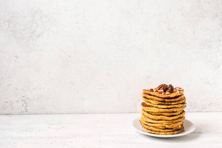 Pumpkin pancakes with pecan and honey on white table, copy space. Traditional autumnal healthy breakfast - stack of pumpkin pancakes. Stock Photo