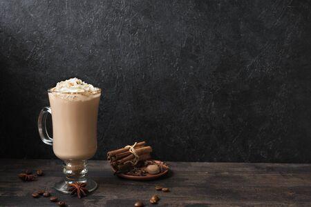 Irish Coffee con panna montata, spezie e chicchi di caffè su fondo di legno nero, copia dello spazio.