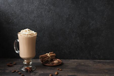 Irish Coffee with whipped cream, spices and coffee beans on black wooden background, copy space.