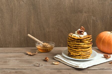 Pumpkin pancakes with whipped cream, pecan and honey on wooden table, copy space. Traditional autumnal healthy breakfast - stack of pumpkin pancakes. 版權商用圖片