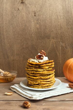 Pumpkin pancakes with whipped cream, pecan and honey on wooden table, copy space. Traditional autumnal healthy breakfast - stack of pumpkin pancakes. Stock Photo