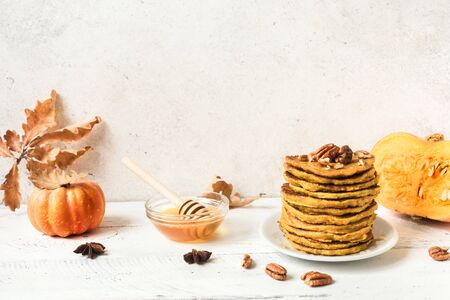 Pumpkin pancakes with pecan and honey and organic pumpkin on white table, copy space. Stack of pumpkin pancakes. Stock Photo