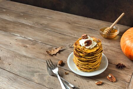 Pumpkin pancakes with whipped cream, pecan and honey on rustic background, copy space. Traditional autumnal healthy breakfast - stack of pumpkin pancakes.