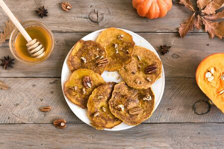 Pumpkin pancakes with pecan and honey on wooden table, top view, copy space. Traditional autumnal healthy breakfast - pumpkin pancakes. Stock Photo