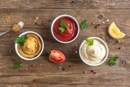 Three classic sauces  ketchup, mayonnaise and mustard on wooden background. Set of popular american sauces, top view, copy space.