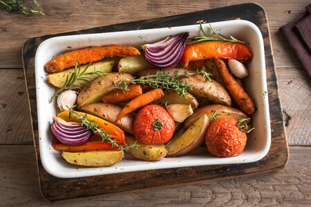 Oven roasted vegetables with spices and herbs in baking dish on wooden, top view. Vegetarian organic autumn meal - baked vegetables.