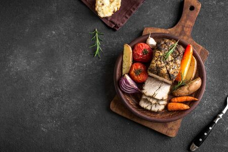 Oven Roasted Meat and Vegetables. Roast Pork Dinner with seasonal vegetables and herbs on black background, top view, copy space. Banco de Imagens