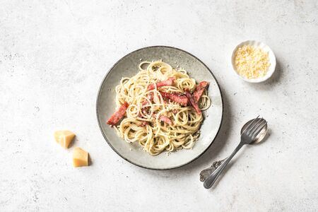 Pasta Carbonara, spaghetti with bacon, egg, hard parmesan cheese and cream sauce. Traditional italian Pasta alla carbonara on white, top view, copy space.