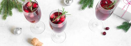 Christmas red cranberry mimosa with rosemary on white background, copy space, banner. Cocktail with champagne for Christmas morning.