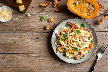 Pumpkin and Bacon Pasta with grated parmesan cheese. Homemade spaghetti pumpkin pasta on wooden, copy space. Seasonal autumn food. Pasta Pumpkin Carbonara. Banco de Imagens