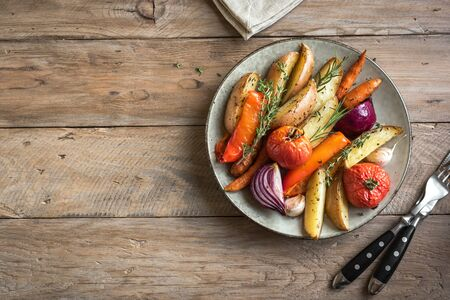 Oven roasted vegetables with spices and herbs on wooden, top view, copy space. Vegetarian vegan organic autumn meal - baked vegetables. Banco de Imagens