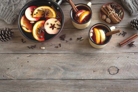 Mulled Wine for winter season. Hot mulled wine drink with fruits and spices on wooden background, top view, copy space.