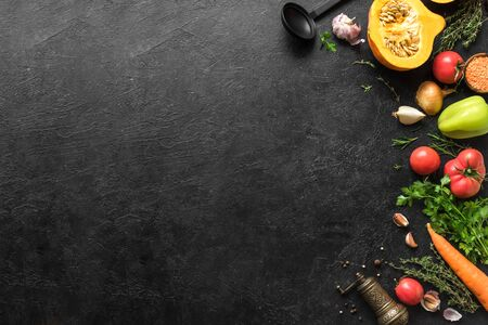 Autumn cooking background with seasonal organic vegetables, herbs on black, top view, copy space. Ingredients for healthy vegetarian vegan seasonal soups and dishes.