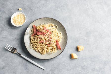 Carbonara pasta, spaghetti with bacon, egg, hard parmesan cheese and cream sauce. Traditional italian cuisine. Pasta alla carbonara, top view, copy space.