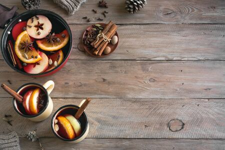 Mulled Wine for winter holidays. Hot mulled wine drink with fruits and spices on wooden background, top view, copy space.