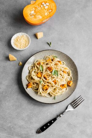 Pumpkin Pasta on concrete background, top view, copy space. Seasonal vegetarian spaghetti pasta with roasted pumpkin, cream, grated parmesan and sage leaves.