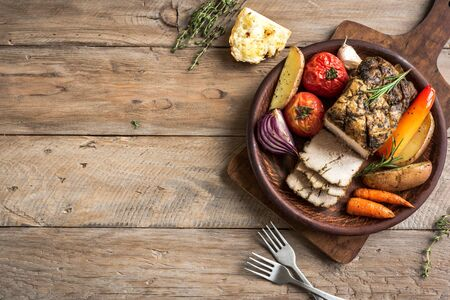 Oven Roasted Meat and Vegetables. Roast Pork Dinner with seasonal vegetables and herbs on wooden background, top view, copy space. Banco de Imagens