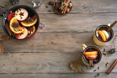 Mulled Wine for Thanksgiving and autum holidays. Hot mulled wine drink with fruits and spices on wooden background, top view, copy space.