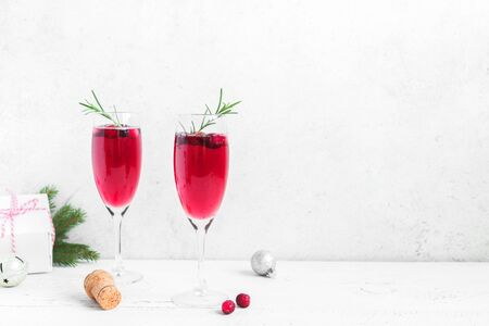 Cranberry mimosa with rosemary and christmas decor on white background, copy space. Cocktail with champagne for Christmas morning.