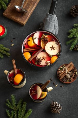 Christmas Mulled Wine for winter holidays. Hot mulled wine drink with fruits and spices on black background, top view, copy space.