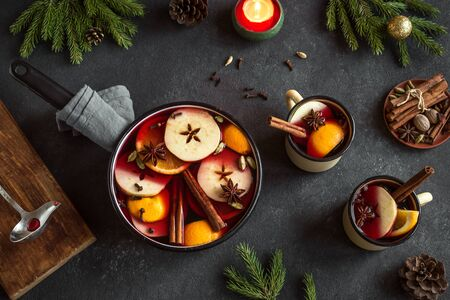 Christmas Mulled Wine for winter holidays. Hot mulled wine drink with fruits and spices on black background, top view.