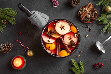 Mulled Wine for Christmas and winter holidays. Hot mulled wine drink with fruits and spices and Christmas decor on black background, top view.