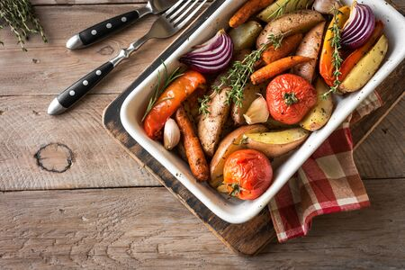 Oven roasted vegetables with spices and herbs in baking dish on wooden table. Vegetarian vegan  healthy organic autumn meal - baked vegetables.