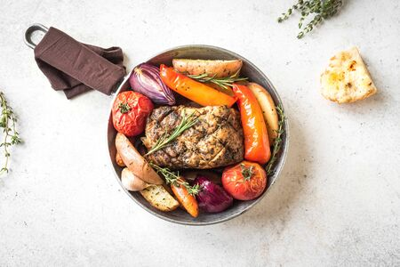 Roasted meat and vegetables on white background, top view, copy space. Oven baked pork and seasonal vegetables and herbs.