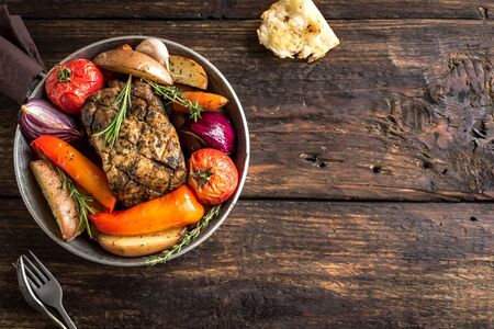 Roasted meat and vegetables on wooden background, top view, copy space. Oven baked pork and seasonal vegetables and herbs. Banco de Imagens