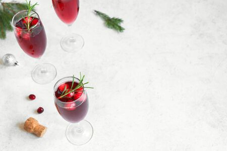 Christmas red cranberry mimosa with rosemary on white background, copy space. Cocktail with champagne for Christmas morning.