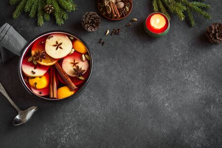 Mulled Wine for Christmas and winter holidays. Hot mulled wine drink with fruits and spices in casserole on black background, top view, copy space.