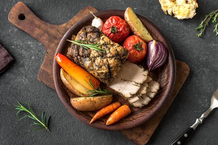 Oven Roasted Meat and Vegetables. Roast Pork Dinner with seasonal vegetables and herbs on black background, top view. Banco de Imagens