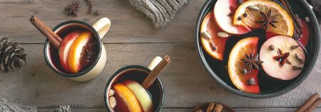 Mulled Wine for winter season. Hot mulled wine drink with fruits and spices on wooden background, top view, banner.
