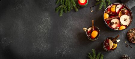 Mulled Wine for Christmas and winter holidays. Hot mulled wine drink with fruits and spices on black background, top view, copy space.