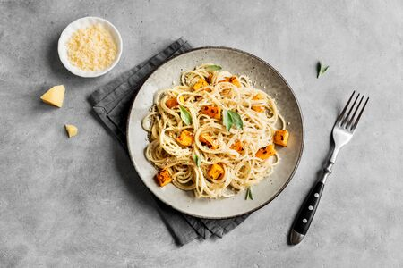 Pumpkin Pasta on concrete background, top view, copy space. Seasonal vegetarian spaghetti pasta with roasted pumpkin, cream, grated parmesan and sage leaves. Banco de Imagens