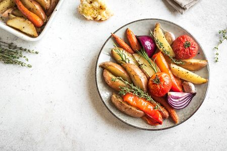 Oven roasted vegetables with spices and herbs on white, top view, copy space. Vegetarian vegan organic autumn meal - baked vegetables.