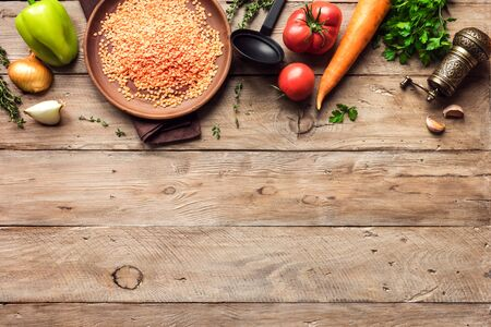 Cooking background with red lentil, seasonal organic vegetables on wooden table, top view, copy space. Ingredients for healthy seasonal vegetarian vegan soups and dishes.